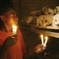 The unknown victims: Rwandan genocide survivor Apollan Odetta lights candles at a mass grave in Nyamata on April 6, 2004. | AP