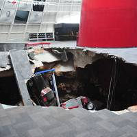 Pit stop: Cars are visible from the edge of a sinkhole Wednesday at the National Corvette Museum in Bowling Green, Kentucky. The museum said eight cars were damaged when the sinkhole opened up early Wednesday morning. | AP