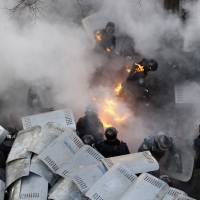 Policemen are pelted with Molotov cocktails during battles with anti-government protesters in front of the Ukrainian Parliament in Kiev on Tuesday.  | AFP-JIJI