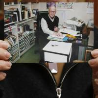 A photo of Australian missionary John Short is displayed by his wife, Karen, at the Christian Book Room in Hong Kong on Wednesday following his arrest in North Korea. | AP