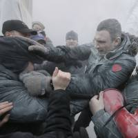 Street fight: Ukraine opposition leader and former WBC heavyweight boxing champion Vitali Klitschko (center) is attacked and sprayed with a fire extinguisher as he tries to stop the clashes between police and protesters in central Kiev on Jan. 19. | AP