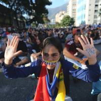 A young demonstrator taking part in a rally in Caracas on Sunday shows the Spanish word for peace written on her hands. | AP