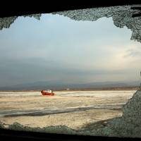 A boat is seen through the shattered window of another abandoned vessel, both stuck in solidified salt at Lake Oroumieh, northwestern Iran, on Sunday. Oroumieh, one of the biggest saltwater lakes on Earth, has shrunk more than 80 percent to 1,000 sq. km in the past decade. | AP