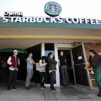 Playing dumb: People line up at 'Dumb Starbucks' coffee — a store resembling a Starbucks with its green awning and mermaid logo, but with the word 'Dumb' attached above the Starbucks sign — in Los Angeles on Monday. | AP