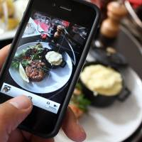A diner at a restaurant in Paris takes a picture of his lunch with a smartphone in order to share it on the Food Reporters network. | AFP-JIJI