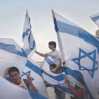 Youths wave the Israeli national flag before praying at the Western Wall in Jerusalem to mark Independence Day in May 2011. The notion of Israel's 'Jewishness' has gained currency and controversy due to Prime Minister Benjamin Netanyahu's demand for explicit Palestinian recognition, and an Israeli group's plans to lobby the Knesset to declare Israel a Jewish state by law. | AP