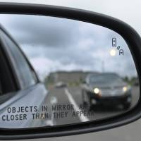 Getting closer: A warning signal in the side mirror of a Ford Taurus is seen at an automobile testing area in Oxon Hill, Maryland. | AP
