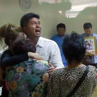 Tayakorn Yos-ubon, the father of two children killed a grenade attack at an anti-government protest site in Bangkok on Sunday, is embraced by family members Monday as he cries during a visit to a hospital to collect their bodies. | AP