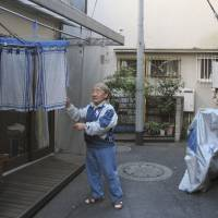 Takeshi Onodera, a retiree who helps run a coffee shop at NPO Moyai in central Tokyo, dries towels Jan. 29 outside the social support center, where homeless people and others who have fallen on hard times get help finding housing and other aid. | AP