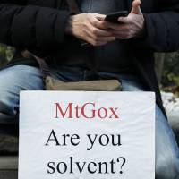 A client protests at a building housing the headquarters of bitcoin exchange Mt. Gox in Tokyo Tuesday. | BLOOMBERG