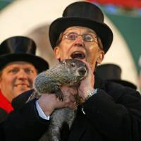 Doubt of a shadow: The groundhog Punxsutawney Phil is held after emerging from his burrow Sunday on Gobbler's Knob in Punxsutawney, Pennsylvania, to forecast the next six weeks of weather. | AP