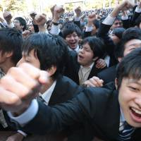 Vocational school students raise their fists during a rally in Tokyo to start off their hunt for a job in January | BLOOMBERG