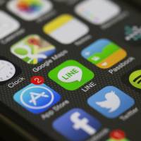 An icon for Line Corp.'s Internet messaging and calling service, controlled by Naver Corp., is displayed with other app icons on an iPhone 5s in Hong Kong on Tuesday. | BLOOMBERG