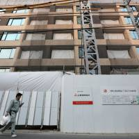 High-riser: A worker walks past the Parkhouse Grand Minamiaoyama Takagicho residential building being developed by a unit of Mitsubishi Estate Co. in Tokyo on Monday. | BLOOMBERG