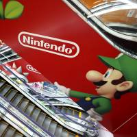 A customer rides past a Nintendo Co. advertisement on an escalator at an electronics retailer in Tokyo in April 2013. | BLOOMBERG
