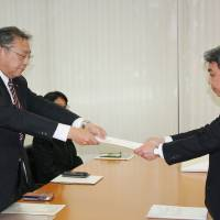 A Toshiba Corp. labor union representative hands a letter containing its demands for this year's 'shunto' spring labor offensive to Toshiba Director Fumiaki Ushio last week. | KYODO