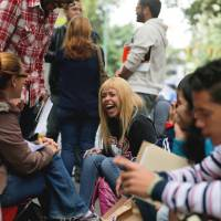 Seeking a brighter future: Daniela Rodriguez laughs with friends as she waits outside the Irish Consulate in Caracas on Tuesday. | AP