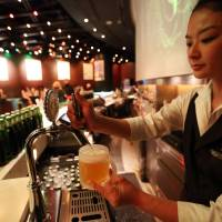 Have a cold one: A bartender fills a glass with Kirin Holdings Co.'s Heartland beer at a bar in the Roppongi Hills complex in Tokyo on April 17, 2013. | BLOOMBERG