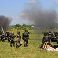 No end in sight: Philippine soldiers fire 105mm howitzer canons toward rebels during a clash near Rajah Buayan, Maguindanao province, on Jan 28. | AFP-JIJI