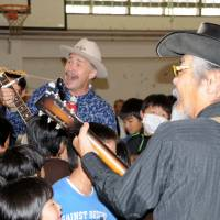 Morale mission: Steve Gardner performs during a recent visit to the Fukushima No. 1 Elementary School in Fukushima city with Shinjiro Mori. | JUN HASEGAWA