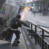 A National Guard member clashes with anti-government protesters in Caracas on Saturday. | AFP-JIJI
