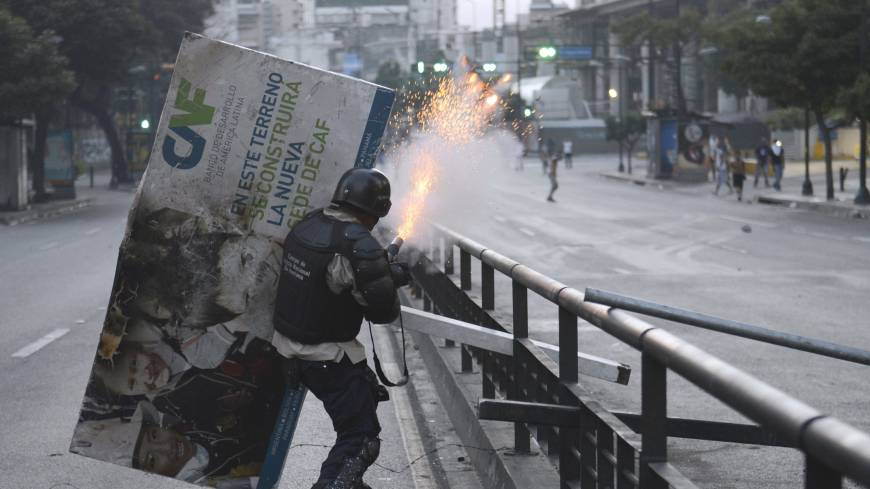 A National Guard member clashes with anti-government protesters in Caracas on Saturday.