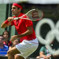 Cruise control: Roger Federer plays a shot from France's Julian Benneteau in a second-round match at Wimbledon on Monday. | AFP-JIJI