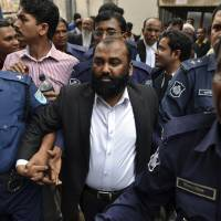 Surrender: One of the two owners of Tazreen Fashions Ltd., Delwar Hossain, is escorted by security personnel to a court in Dhaka on Sunday. | AP