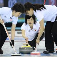 Brushed aside: Yumie Funayama (center) throws a stone during Japan's 8-4 defeat to Sweden in its final round-robin match at the Sochi Olympics on Monday. | AFP-JIJI