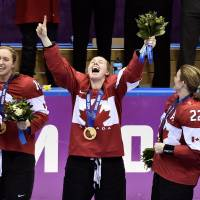 On top of the world: Members of the Canadian women's hockey team celebrate after winning gold at the Sochi Olympics on Thursday. | AP