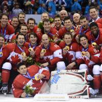 On top of the world: The Canadian hockey team poses for pictures after defeating Sweden to claim the gold medal on the final day of the Sochi Olympics on Sunday. | AFP-JIJI