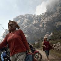 Dusty death: Residents run from hot volcanic ash clouds engulfing villages in Karo district during the eruption of Mount Sinabung volcano in Sumatra Island, Indonesia, on Saturday. Fourteen people, including four schoolchildren, were killed after being enveloped by the scorching ash clouds spat out by the volcano in its biggest recent eruption, officials said. | AFP-JIJI