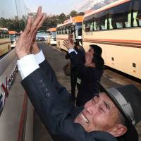North Koreans wave as buses carrying their South Korean relatives depart the resort area of Mount Kumgang on Saturday, the third and final day of the first group of family reunions between North and South Korea. | AFP-JIJI