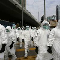 New strain: Health workers in full protective gear walk at a wholesale poultry market before a culling in Hong Kong on Jan. 28. Chinese scientists voiced concern Wednesday over the spread of a new bird flu virus that killed an elderly woman in December and infected another individual last month. | AP