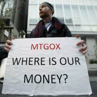 London-based Kolin Burges holds a placard while protesting outside headquarters of the Mt. Gox bitcoin exchange and its parent company, Tibanne Co., in Tokyo on Tuesday. | BLOOMBERG