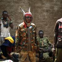 Ready to strike: Anti-Balaka militiamen gather in Bangui on Tuesday. Fighting between Muslim Seleka militias and Christian anti-Balaka factions continues in the Central African Republic as French and African Union forces struggle to contain the bloodshed. | AP