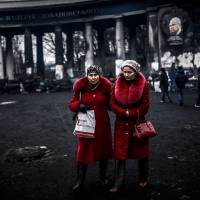 Women walk in front of the Dynamo Kiev stadium in Kiev on Tuesday. Ukraine's interim leader has delayed the appointment of a new unity government until Thursday as the country seeks to find a way out of its most serious political crisis since independence. | AFP-JIJI