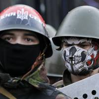 Ukrainian anti-government protesters man a barricade in Kiev on Friday ahead of the signing of a deal with President Viktor Yanukovich that EU foreign ministers brokered to resolve the country's political crisis. | REUTERS