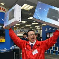 A worker at a Tokyo electronics store promotes the release of the Sony PlayStation 4 video-game console on Saturday. | AFP-JIJI