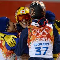 Together we stand: Reruhi Shimizu (left) Noriaki Kasai (center) and Taku Takeuchi celebrate in the finish area during the men's ski jumping large hill individual final round on Saturday. | AFP-JIJI