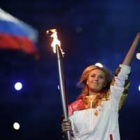 Leader of the pack: Russia's Maria Sharapova carries the torch during the opening ceremony for the 2014 Winter Olympics in Sochi, Russia, on Friday. | AP