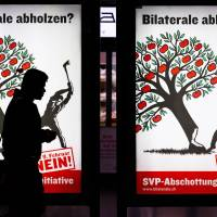 Immigration ire: A man walks past an electoral poster against the 'Stop Mass Immigration' referendum by the right-wing populist Swiss People's Party in Zurich on Thursday. | AFP-JIJI