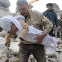 Yet another victim: A Syrian man carries a person's body from the remains of a destroyed building following air raids by government forces on the rebel-held part of Aleppo's Maadi residential district Wednesday. | AFP-JIJI