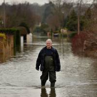 Stranded: A resident walks through floodwaters in Wraysbury, England, on Monday. The U.K. Environment Agency has some 14 severe flood warnings in place along the River Thames, as continued rainfall pushed water levels along some stretches of the river to record levels. | AFP-JIJI