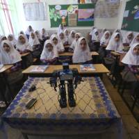 Veldan, a humanoid praying robot built by Iranian schoolteacher Akbar Rezaie, performs morning prayer in front of Alborz elementary school girls in the city of Varamin, near Tehran, on Monday. | AP