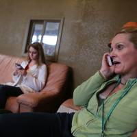 Marijuana store owner Toni Fox speaks on the phone with a reporter as her daughter and employee Cheyenne texts in the lobby of Fox's 3D Cannabis Center in Denver on Friday. Fox and others in the marijuana industry breathed a sigh of relief Friday after federal banking regulators issued long-awaited permission for them to access basic banking services. | AP