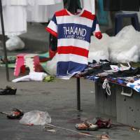 A souvenir T-shirt proclaiming Thailand the 'Land of Smile' hangs at the scene of an explosion at a protest site in Bangkok on Sunday. | AP