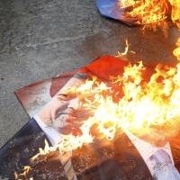 A portrait of Turkey's Prime Minister Tayyip Erdogan burns Tuesday during a demonstration against the opening of a new road running through the Middle East Technical University campus in Ankara. | REUTERS