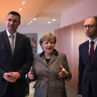 German Chancellor Angela Merkel talks with Ukrainian opposition leaders Vitali Klitschko (left) and Arseniy Yatsenyuk at the chancellery in Berlin on Monday. | AFP-JIJI
