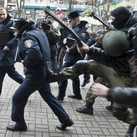 Anti-government protesters attack police in front of Kiev's City Hall on Sunday. Ukraine on Monday granted amnesty to opposition protesters after they agreed to end their occupation of City Hall and other public buildings and partially dismantle barricades. | AFP-JIJI